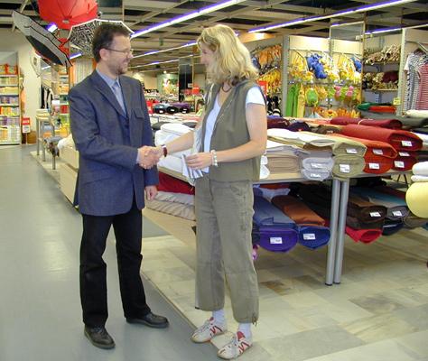 Výherkyní předchozí amatérské soutěže v šití se stala paní Alexandra Hartmanová z Jihlavy. Na snímku jí gratuluje vedoucí OD Prior v Českých Budějovic Vladimír Florian.