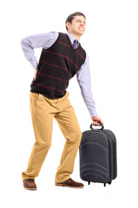 Man lifting his luggage and suffering from a back pain