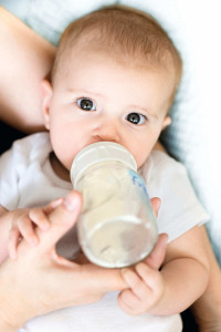 Baby drinking from bottle --- Image by © Ocean/Corbis