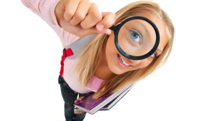 Funny Schoolgirl Looking Through The Magnifying Glass