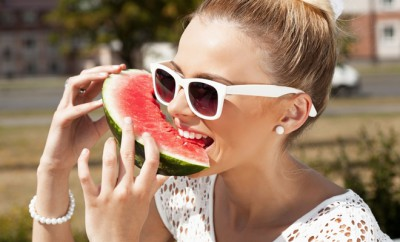 Sexual woman takes watermelon from the opened fridge full of vegetables and fruit. Concept of healthy and dieting food