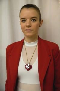 Elegantním módním doplňkem je červené srdíčko na bílém svetříku s červeným kostýmem