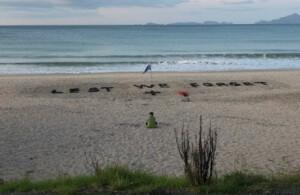 Žena si připomíná v roce 2020 ANZAC Day na mořském břehu na Novém Zélandu